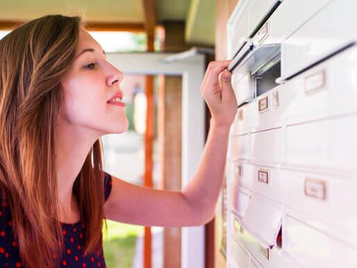 woman peeking in a mailbox